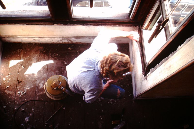 David Ireland cleaning the window frame of the front parlor room at 500 Capp Street, c.1976; photo: Steven Kayfetz; image courtesy of The 500 Capp Street Foundation.