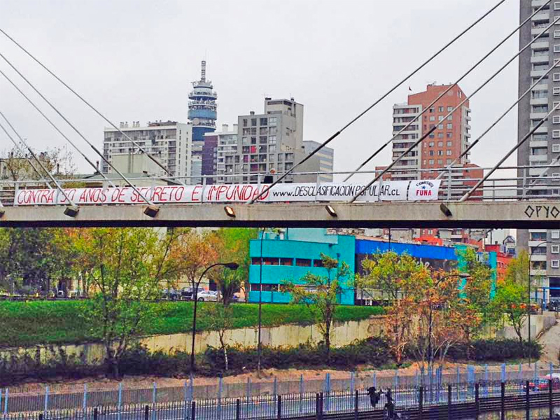 "Banner hanging from a bridge in Santiago, Chile directs passers-by to the Popular Declassification website — ""Against 50 years of secrecy and impunity."""