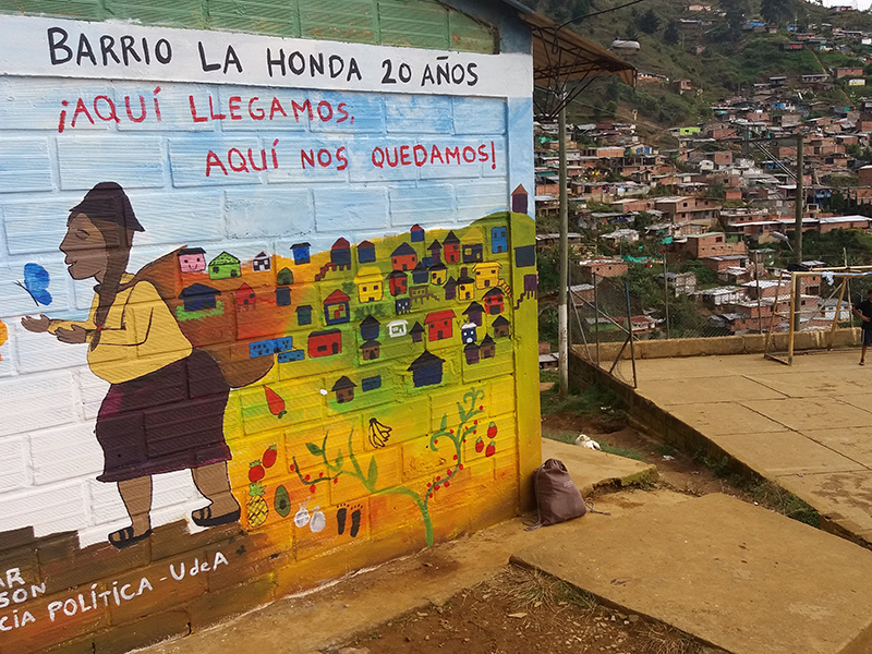 A mural painted by community members in the La Honda neighborhood in Medellín. The neighborhood is primarily composed of families displaced from rural areas in the state of Antioquia. The inhabitants are being forced to resist again in order to avoid being displaced (again) by the state. Photo credits: James Granada, Master of political science, Universidad de Antioquia.