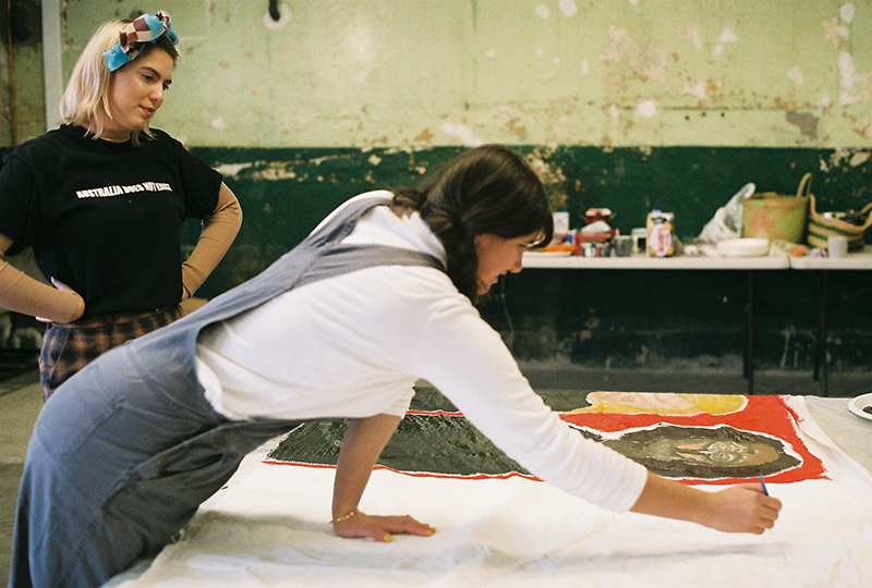 Kate ten Buuren and Kalyani Mumtaz painting banner for Because of Her, We Can: HEAL exhibition. Photo: Natalie Ironfield.