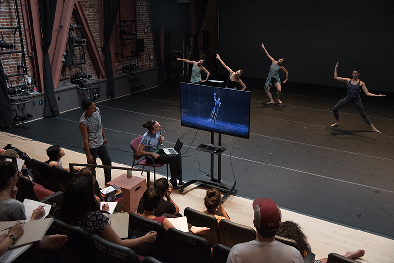 The commissioned artists watch footage from the Cunningham archives while the dancers rehearse on stage.