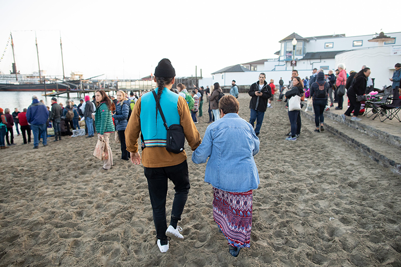 Julian Brave NoiseCat and Ruth Orta walk along the Aquatic Park shore at the Alcatraz Canoe Journey. Photo: Marissa Leshnov.