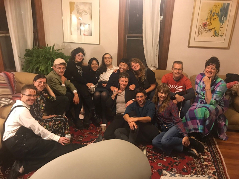 From left to right: Ted Rees, Olive Blackburn, JJ Mull, Sara Wintz, Trisha Low, Zoe Tuck, Cheena Marie Lo, Tessa Micaela, Rebecca Maillet, Syd Staiti, Stephanie Young, Clay Banes, and Brittany Billmeyer-Finn. Pictured in Zoe and Brittany's living room in Northampton, MA on Friday, October 25, 2019, when Ted, Trisha, Syd, and Stephanie visited from the Bay Area to read from their books. Ted, Olive, JJ, Sara, Cheena, Tessa, Rebecca, Clay, Brittany, and Zoe met in the Bay Area and live constellated across MA, VT, RI, and PA now. Photo by Jay Weingarten.