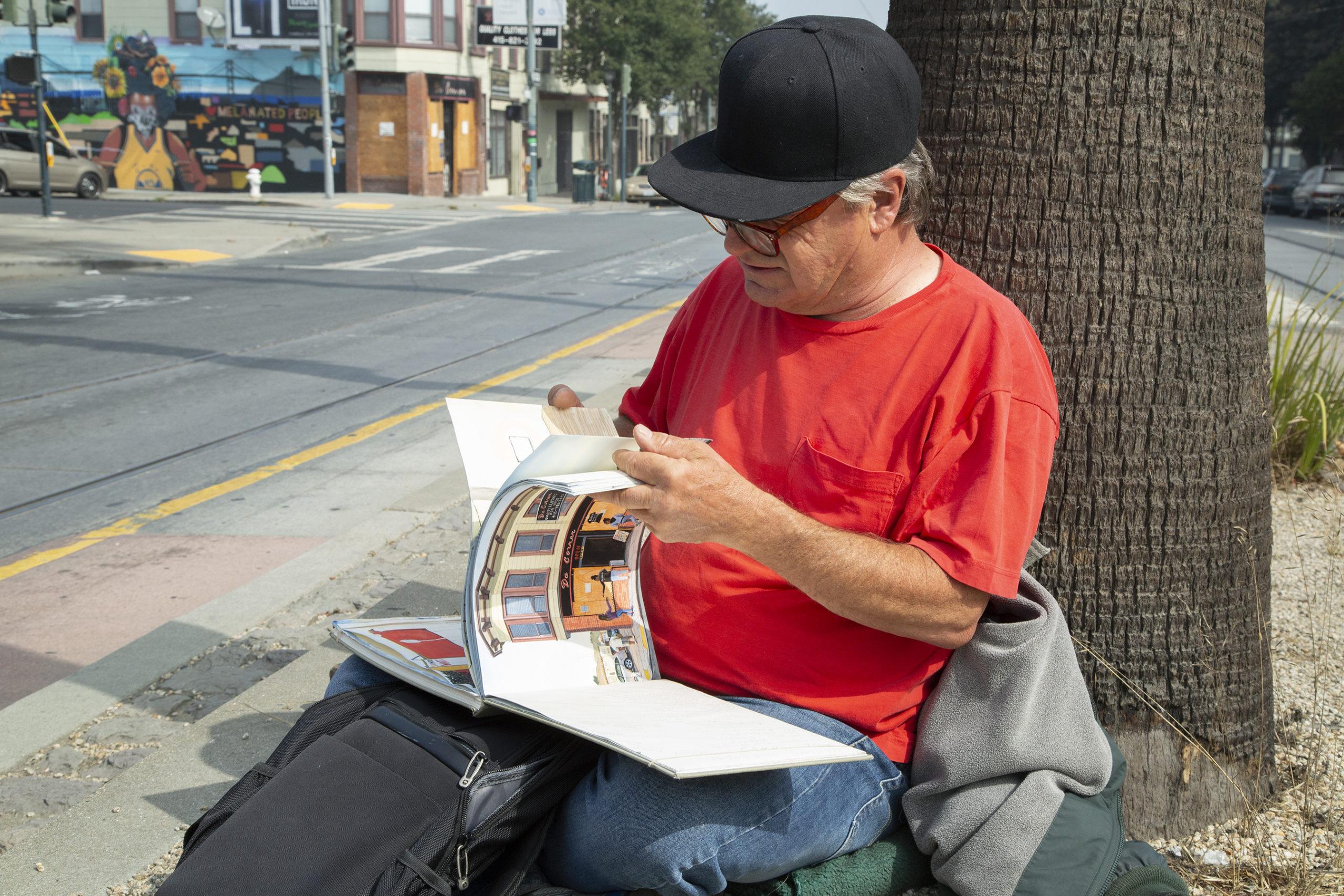 Rico Salinas looking through sketchbook