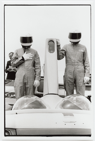"The Artist-Dummies, Curtis Scheier and Doug Michels, standing astride the tail-fin of the Phantom Dream Car as ""The Star Spangled Banner"" is played. Photograph by Diane Andrews Hall. From the Ant Farm Archive, housed at the Berkeley Art Museum and Pacific Film Archive."