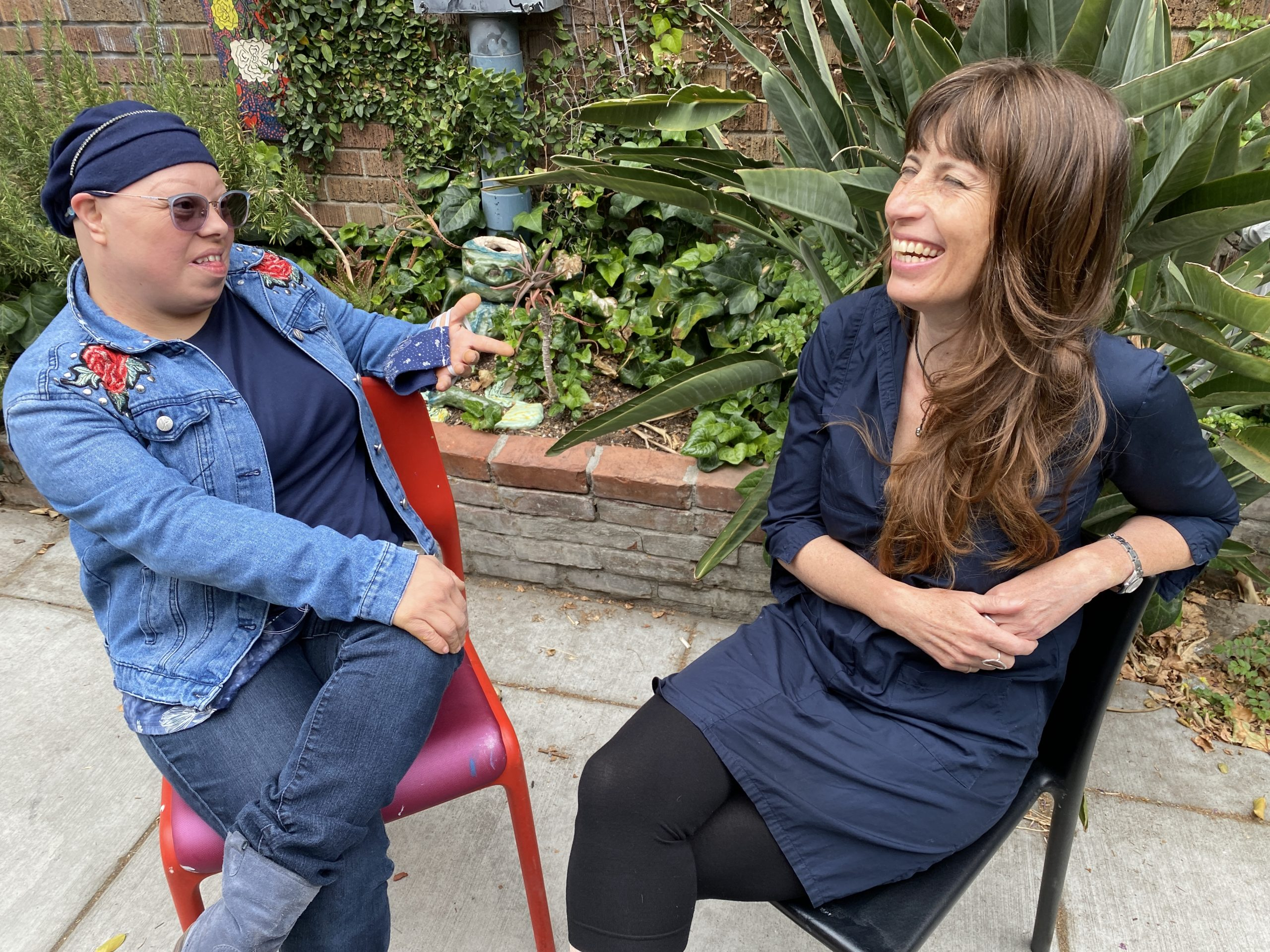 Creative Growth artist and poet Elizabeth Rangel and poet Lorraine Lupo smile as they sit and chat in a garden filled with plants and ceramics outside of a red brick studio building.
