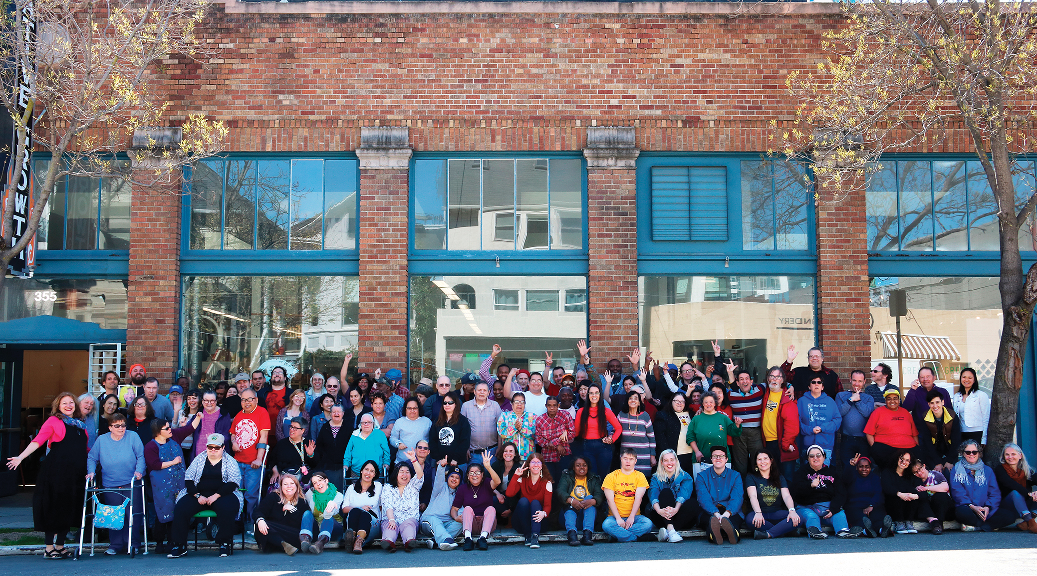 A crowd of eighty to one hundred Creative Growth artists, poets, and staff pose for a group photo in front of the Creative Growth Art Center, a brick building with large windows. Everyone is standing except for the front row of people seated. Many people are smiling, waving, and holding up peace signs.